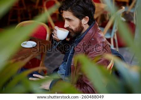 Side view through plant leaves, pensive fashionable hipster man holding cup of tea or coffee next to his mouth while sitting on the terrace of beautiful coffee shop - stock photo