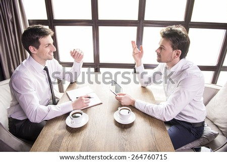 Side view. Two young businessmen discussions of work during a business lunch. - stock photo