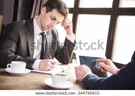 Side view. Two young businessmen working during a business lunch. - stock photo