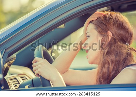 Side view window portrait displeased young stressed angry pissed off woman driving car annoyed by heavy traffic. Emotional intelligence concept. Negative human face expression - stock photo
