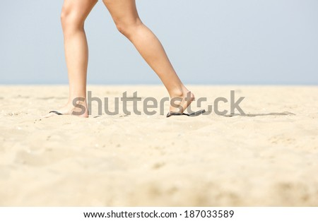 Side view woman walking in sandals on sand at the beach - stock photo