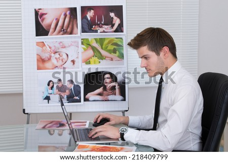 Side view young male photo editor using laptop at desk in office - stock photo
