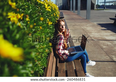Side view young student girl sitting in front of a laptop outside and enjoying sunny day on campus, charming woman using computer while sitting on wooden bench - stock photo