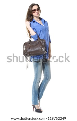 Side view young stylish slim in jeans with handbag posing - stock photo