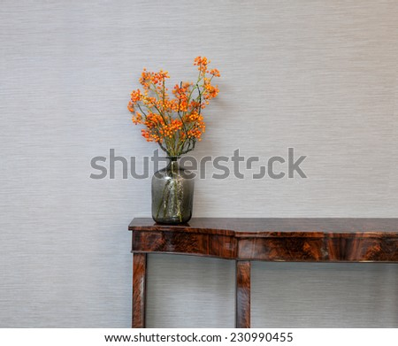 Sideboard in front of a grey wall with orange flower vase - stock photo