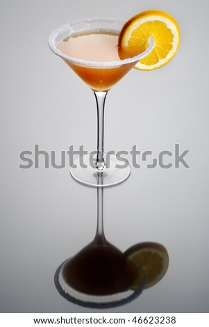 Sidecar mixed drink with orange garnish and sugar rim on plain grey background - stock photo