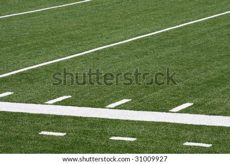 Sideline segment of a turf-covered athletic field with line markings.