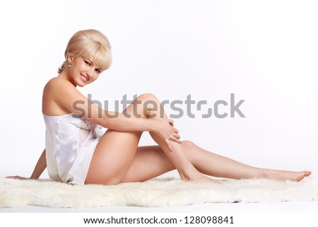 sideview full-length portrait of beautiful young blonde woman in lingerie sitting on white fur carpet