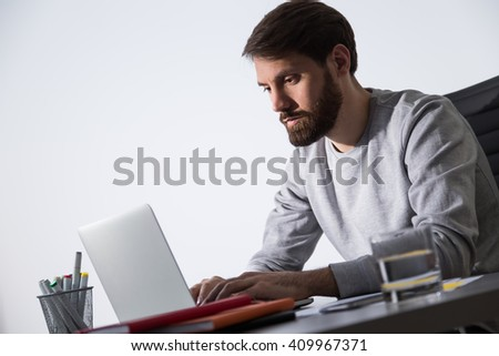 Sideview of bearded caucasian businessman working on laptop at office desk with glass of water and office tools - stock photo