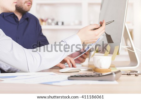 Sideview of businessmen discussing business charts and pointing at computer screen in office - stock photo