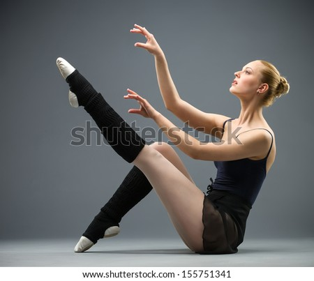 Sideview of dancing on the floor ballerina with her leg up, isolated on grey. Concept of elegant art and sportive hobby - stock photo