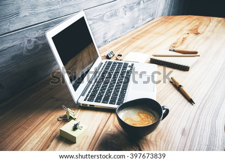 Sideview of laptop and different office tools on wooden desktop