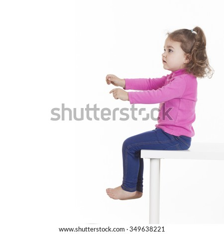 Sideview of little girl sitting on chair against of white background. Isolated, studio shot - stock photo