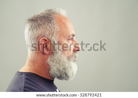 sideview of senior bearded man over light grey background with empty copyspace - stock photo