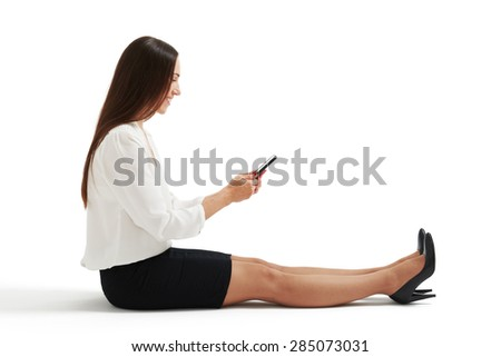 sideview photo of woman in formal wear sitting on the floor and using her smartphone. isolated on white background - stock photo