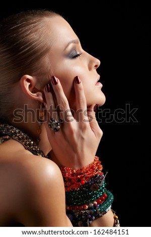 sideview portrait of beautiful young brunette woman in multiple bracelets on dark gray - stock photo