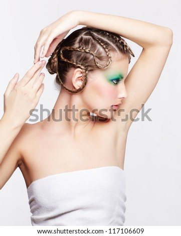 sideview portrait of beautiful young dark blonde woman with creative braid hairdo posing on gray with hands over head