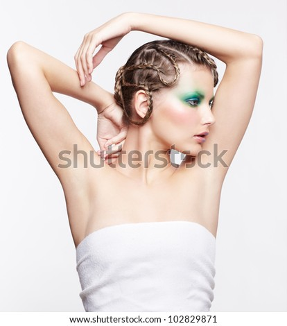 sideview portrait of beautiful young dark blonde woman with creative plait hairdo posing on gray with hands over head