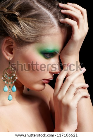 sideview portrait of beautiful young woman with green and blue eye shade make-up posing on black