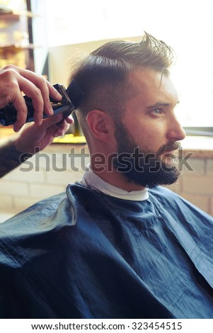 sideview portrait of handsome man in a barber shop. barber cutting hair with electric clipper and comb  - stock photo