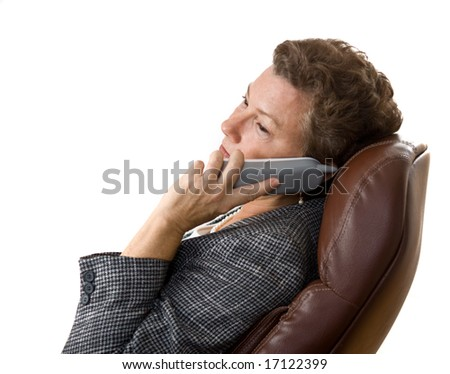 Sideview portrait of mature executive businesswoman on the telephone at her desk - stock photo