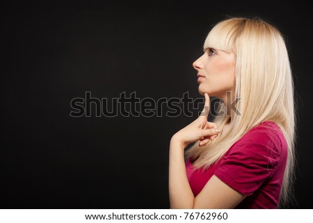 Sideview portrait of young beautiful female with long blond hair with finger on the chin - stock photo