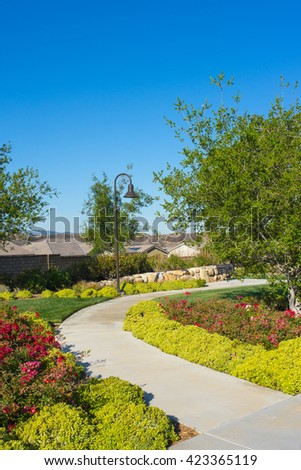 Sidewalk bends around a corner of flowers and tree. - stock photo
