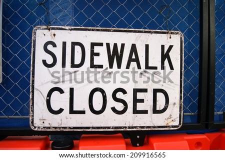 sidewalk closed sign on fence - stock photo