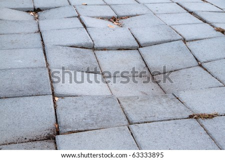 Sidewalk of concrete tiles that are starting to sink and have created a depression - stock photo