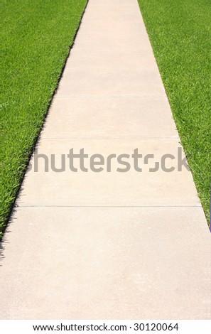 Sidewalk passage in green grass - stock photo