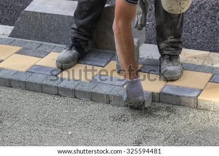 Sidewalk paver installation in progress. Sidewalk revitalization. Focus on hands. - stock photo