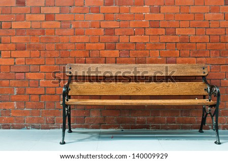 sidewalk scene with wooden bench and brick wall - stock photo