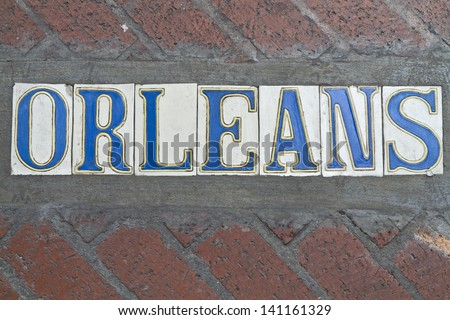 SIdewalk street sign for Rue Orleans in the French Quarter of New Orleans, Louisiana - stock photo