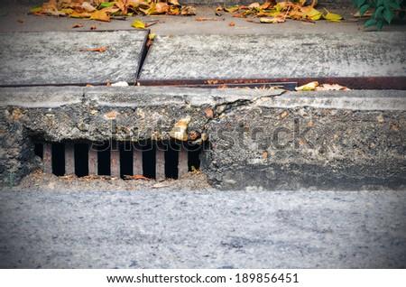 Sidewalk with a street drainage - stock photo