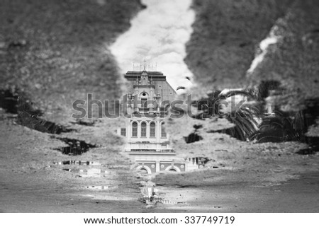 Sidewalk with puddles of water and mirroring black and white image - stock photo