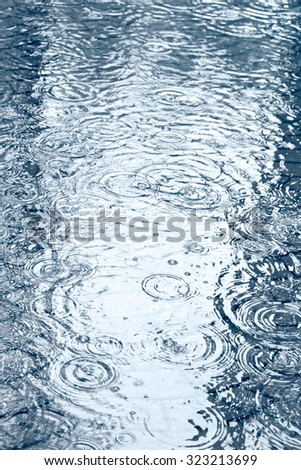 sidewalk with puddles of water and raindrops during heavy rain soft focus - stock photo