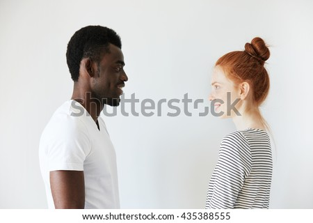 Sideways portrait of a happy couple staring at each other in white morning room. Afro Amercian man in white shirt and redhead girl in stripped longsleeve smiling, showing positive emotions and joy. - stock photo