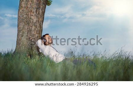 Sideways - profile of young man listen music - enjoy - repose in grass. Guy leaning against a tree relaxing - resting. Outdoors - outside. Carefree - stock photo