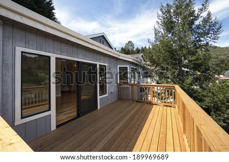 Sideways view of beautiful wood balcony deck with sliding doors and view - stock photo