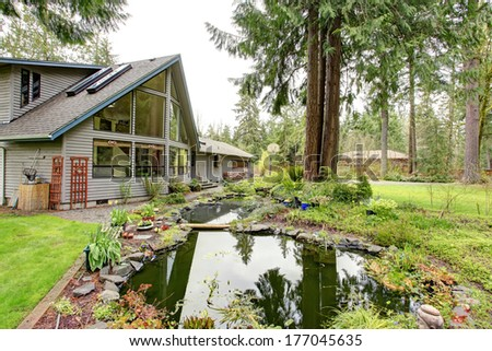 Siding countryside house with glass wall overlooking man made pond with wooden bench - stock photo