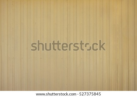 Siding, metal vertical panels texture closeup in the daytime outdoors. Metal wall or fence embossed metal sheets. Terrain and large metal sheet as a barrier or fence