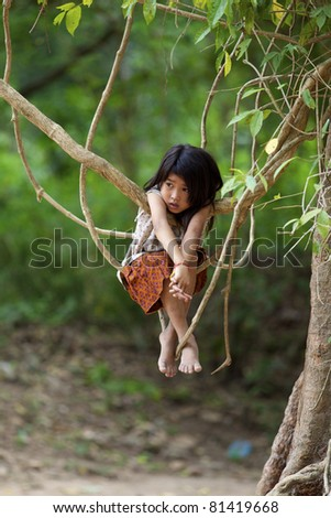 SIEM REAP, CAMBODIA- APRIL 1: Unidentified child plays in jungle at Ta Prohm Temple in Siem Reap, Cambodia on April 1, 2011. Cambodian median age is 23 with 32% of population 14 yrs or younger. - stock photo