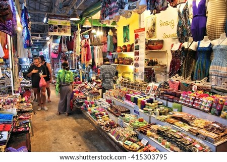SIEM REAP, CAMBODIA - DECEMBER 8, 2013: Unidentified people visit marketplace in Siem Reap. Garment industry of Cambodia accounts for 80 percent of its exports. - stock photo
