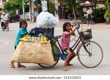 SIEM REAP, CAMBODIA - JUNE 28, 2014: Two local unidentified girls of school age pose for camera carrying large bags with trash on a bicycle. In Khmer family every member must earn money. - stock photo