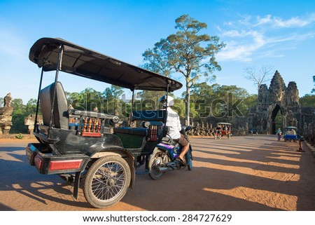 SIEM REAP, CAMBODIA - May 4: Tuk-tuk driver waits for customers at the gate of Angkor Thom on May 4, 2015 in Siem Reap. Tuk-tuks are the most common and popular way to get around Siem Reap.