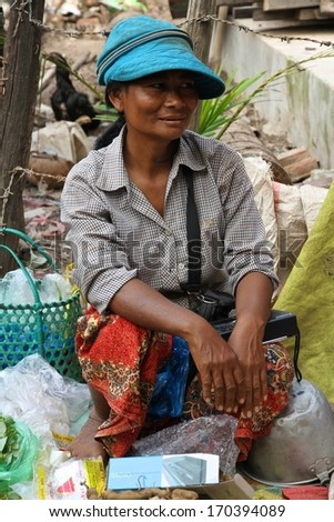 SIEM REAP, CAMBODIA - NOVEMBER 23: A Cambodian woman sitting at a local market near Siem Reap, Cambodia on the 23rd November, 2013.