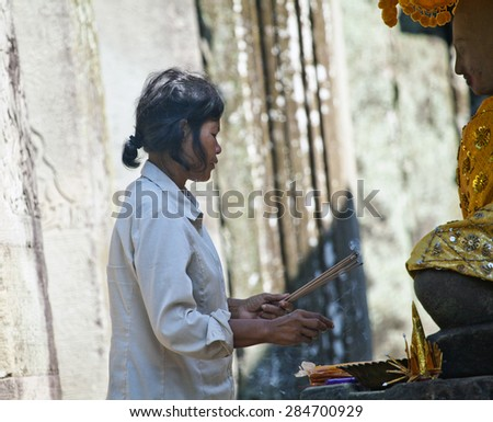 SIEM REAP, CAMBODIA - NOVEMBER 16, 2011: An unidentified woman prays in a Buddhist merit making ceremony at Angkor Wat. Theravada Buddhism is practiced by over 95% of Cambodians. - stock photo