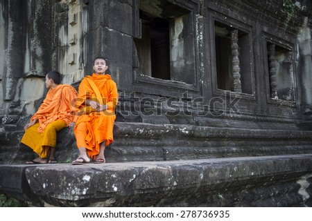 SIEM REAP, CAMBODIA - OCTOBER 30, 2014: Pair of novice Buddhist monks in saffron robes sit on the weathered stone architecture of Angkor Wat temple.