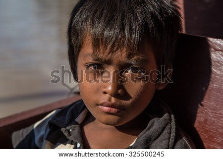 Siem Reap , Cambodia - September 10 , 2015:boat trip in Siem Reap , A kid keep staring at me the whole boat trip in his boat .