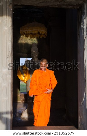 SIEM REAP, CAMBODIA- SEPTEMBER 18: Buddhist novices in Angkor Wat in Siem Reap on September 18, 2011. Buddhism is currently estimated to be the faith of 96% of the Cambodian population. - stock photo